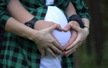mujer embaraza y su pareja formando un corazon encima del vientre de la la madre
