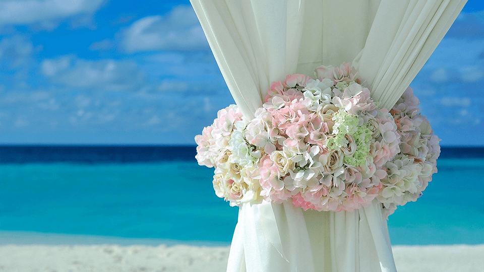 ramo de rosas agarrando cortinas en boda intima con la playa de fondo