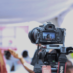 video entrevista a mujer de fondo, camara de video en primer plano